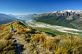 Woman hiking, Dart River Valley and Lake Wakatipu in background, Mount Alfred, Fiordland National Park, UNESCO Welterbe Te Wahipounamu, Queenstown-Lake District, Otago, South island, New Zealand