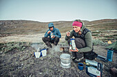 Hiker eating in front of a tent, greenland, arctic.