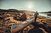 Men carrying a rowing boat in greenland, greenland, arctic.