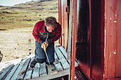 man cutting wood, greenland, arctic.