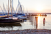 Joung girl goes for a swim at the Sunset at the Ammersee lake, Bavaria, Germany, Europe