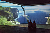 tow visitors watch animated introduction to the Cliffs of Moher at visitor centre, County Clare, Ireland, Europe