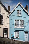 blau gekleidetet Frau vor blauem Deck of Cards Haus (bunte steile Häuser in West View Straße), Cobh, Grafschaft Cork, Irland, Europa