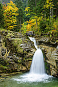 Waterfall with trees in autumn colours in background, Kuhflucht waterfall, Farchant, Ester Mountains, Bavarian Alps, Upper Bavaria, Bavaria, Germany