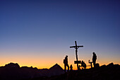 Two persons standing at dawn at cross at summit, Lagazuoi, Dolomites, UNESCO World Heritage Site Dolomites, Venetia, Italy
