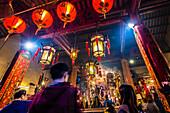 Praying inside the Taoist Man Mo Temple, Hong Kong, China, Asia