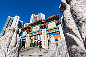 The entrance portal to the Taoist Wong Tai Sin Temple framed by the residential high-rise buildings in Kowloon, Hong Kong, China, Asia