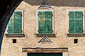 An old house façade with window shutters in a small village on the Wine Route, Margreid, South Tyrol, Alto Adige, Italy
