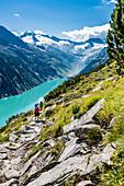 Hikers in the Zillertal Alps with the Schlegeisspeicher reservoir, Ginzling, Zillertal, Tirol, Austria