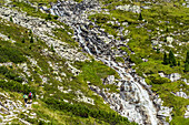 Hikers in the Zillertal Alps with a small waterfall of Riepenbach, Ginzling, Zillertal, Tirol, Austria