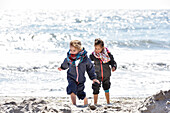 Kids playing at the beach in winter on Baltic Sea, Kellenhusen,  Schleswig Holstein, Germany