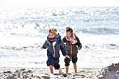Kinder spielen am Strand im Winter an der Ostsee, Kellenhusen, Schleswig Holstein, Deutschland