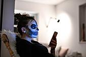 Geschminktes Mädchen mit Handy an Halloween, Hamburg, Deutschland