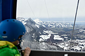 Boy locking outside mountain cable car, Charmey, Switzerland