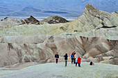 Several persons posing in front of colourful badlands at Death Valley, Death Valley National Park, California, USA