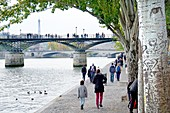 Paris, France. People walking along the north bank of the River Seine, Pont des Arts and Eiffel Tower behind.