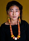 Portrait of a tibetan woman with a huge necklace, Qinghai province, Tsekhog, China.