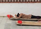 Tibetan pilgrim woman praying and prostrating in Hezuo monastery, Gansu province, Hezuo, China.