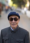 Old man with traditional sunglasses and cap, Gansu province, Linxia, China.
