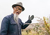 Portrait of an old chinese man with a long white beard in Hezuo monastery, Gansu province, Hezuo, China.
