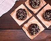 Chocolate muffins are sprinkled with ground nut on pieces of brown paper, top view, empty space on the left.