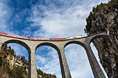 Bernina Express red train along Landwasser Viaduct. Filisur, Graubunden, Switzerland, Europe.
