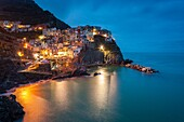 Long exposure of Manarola at dusk. Cinque Terre, Riviera di Levante, Liguria, Italy.