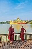 Yangon, Myanmar (Burma). Two monks watching the Karaweik Palace on the Kandawgyi Lake.