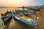 Amarapura, Mandalay region, Myanmar. Colorful boats moored on the banks of the Taungthaman lake at sunrise, with the U Bein bridge in the background.