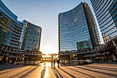 Milan, Lombardy, Italy. People walking in Gae Aulenti square in the Porta Nuova business district at sunset.