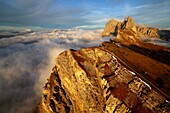 Aerial shot from Seceda of Odle surrounded by clouds at sunset. Dolomites Val Funes Trentino Alto Adige South Tyrol Italy Europe.