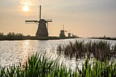 Morning sun just risen shines in the canal where windmills are reflected Kinderdijk Rotterdam South Holland Netherlands Europe.
