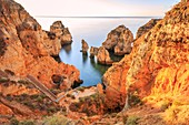 Golden sunrise on the red cliffs of Ponta da Piedade Lagos Algarve Portugal Europe.
