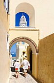 A couple walk under an archway near the St. John the Baptist Cathedral in Fira, Santorini, Cyclades, Greece.