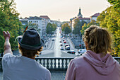 Two young men standing at the Friedensengel, looking over Luitpold Bridge, Munich, Upper Bavaria, Germany
