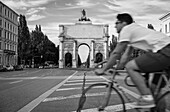 Street scene in front of Siegestor, a cyclist crossing the street, Munich, Upper Bavaria, Germany