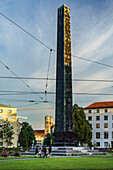 A group of costumed girls crossing the Obelisk at Karolinenplatz, in the back the Frauenkirche, Munich, Upper Bavaria, Germany