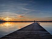 Eine Frau steht auf einem Steg am Ostufer des Starnberger Sees bei Sonnenuntergang, Ambach, Oberbayern, Deutschland
