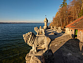 The two lions and the tower of the bathing area of Schloss Seeburg at lake Starnberger see in the setting sun, Muensing, Upper Bavaria, Germany