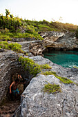BERMUDA. Hamilton Parish. Cliff jumping, swimming off a point in Admiralty House Park in Hamilton.