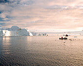 GREENLAND, Ilulissat, Ilulissat Icefjord, fishermen hunting for seals and fish with glaciers in the background