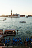ITALY, Venice, Sunrise view of the Grand Canal with water taxis, gondolas and the Chiesa di San Giorgio Maggiore in the background.