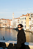 ITALY, Venice. Artist Mia Kaplan on the Rialto Bridge overlooing the Grand Canal.