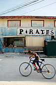 BELIZE, Caye Caulker, a boy rides his bike past pirates restaurant