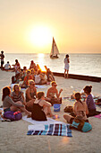 BELIZE, Caye Caulker, tourists enjoy the beach and sunset at the Lazy Lizard Bar