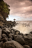 USA, Hawaii, The Big Island, surfer watches the waves on a rocky shoreline at the Hakalau River mouth