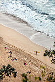HAWAII, Oahu, North Shore, individuals spending time on the beach at Waimea Bay