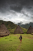 INDONESIA, Flores, a man walks towards his traditional thatched home in Wae Rebo Village, the home is treaditionally referred to as Mbaru Niang