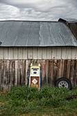 USA, Oregon, Enterprise, an old gas pump leans up against the side of a barn at the Snyder Ranch in Northeast Oregon