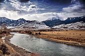 USA, Wyoming, Yellowstone National Park, a majestic ranch sits at the edge of the Yellowstone River outside the North Entrance of the park near Gardnier, Gallatain National Forest and Electric Peak in the distance